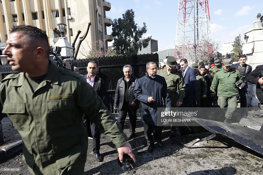 Syrian Minister of Interior Ahmed al-Shaar (C) arrives at the site of a suicide attack at a police officer's club in the Masaken Barzeh district of the capital Damascus on February 9, 2016. The Syrian Observatory for Human Rights said about 20 people had also been wounded, adding that policemen were among the dead and injured. BESHARA