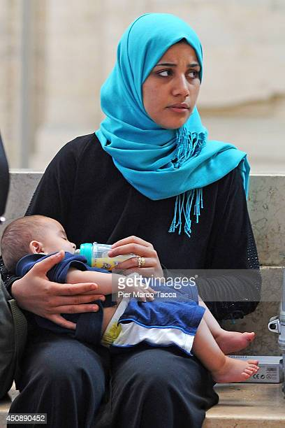 Syrian mother and baby wait along with other Syrian refugees who arrived by train to long lines at the Milano Centrale railway station from southern...