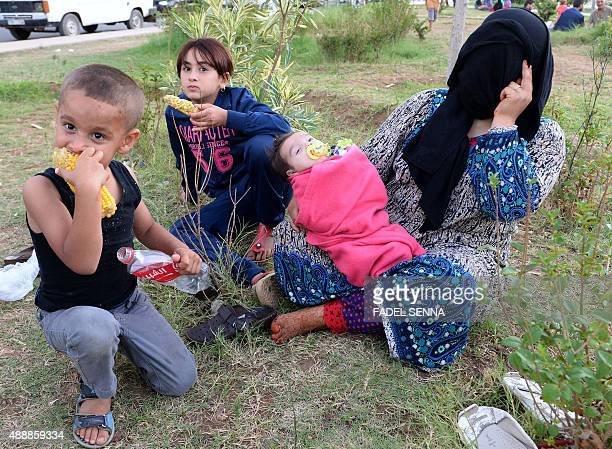 A Syrian mother and her children sit on September 17 2015 at a park where around 1000 Syrians migrants are gathering in the Moroccan town of Nador...
