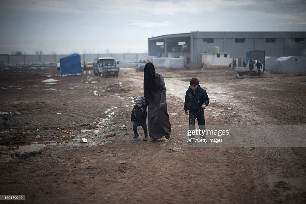 A Syrian mother and her two childern walk through the mud after the first snow of the year fell the previous night at a refugee camp in Bab al-Salama on the Syria-Turkey border, on January 9, 2013. The internally displaced Syrians faced further misery due to increasing shortage of supplies as heavy rain was followed by a drop in temperatures.