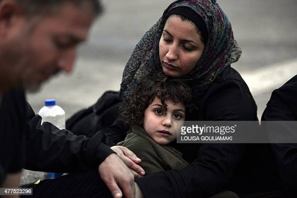 A Syrian mother tries to warm up her daugter after they arrived on the island of Lesbos early on June 18 2015 Some 48000 migrants and refugees have...
