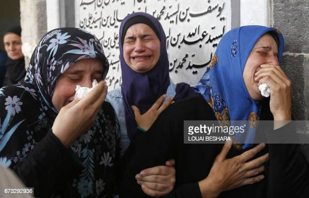 TOPSHOT Syrian mourners attend a funeral ceremony in the Sayyida Zeinab mosque on the outskirts of Damascus on April 26 for the victims of a bombing...