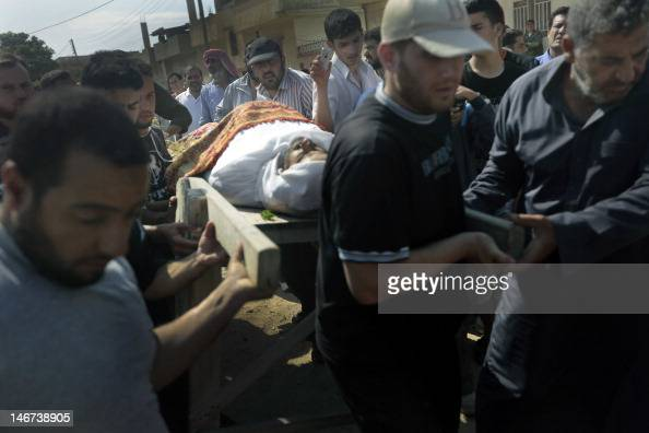 Syrian mourners carry the body of one of the victims of the previous day's shelling on the rebel stronghold of Qusayr outside the flashpoint Syrian...