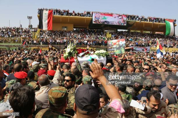 TOPSHOT Syrian mourners wave at the coffin of Brigadier General Issam Zahreddine at a stadium during his funeral in the southern city of Suwaida on...