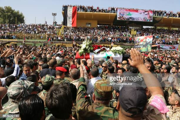 Syrian mourners wave at the coffin of Brigadier General Issam Zahreddine at a stadium during his funeral in the southern city of Suwaida on October...