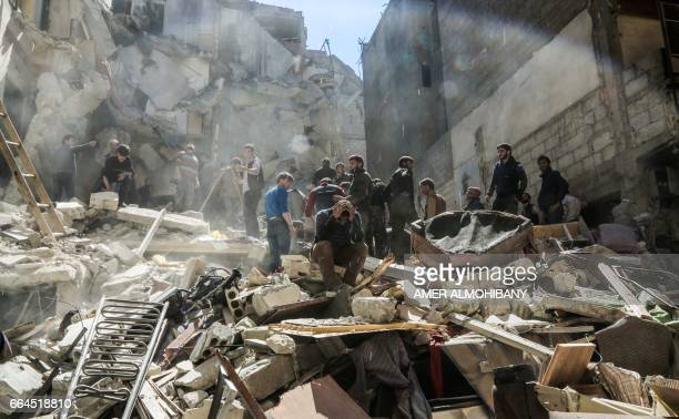 Syrian mourns as members of the Syrian civil defence volunteers also known as the White Helmets and people search for survivors from the rubble...