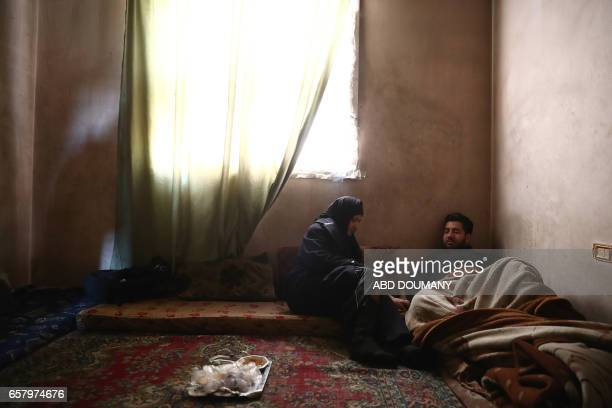 TOPSHOT Syrian Naheel a sixtysixyear old widow who was displaced from the alMaliha area due to the ongoing fighting sits next to her son in her home...