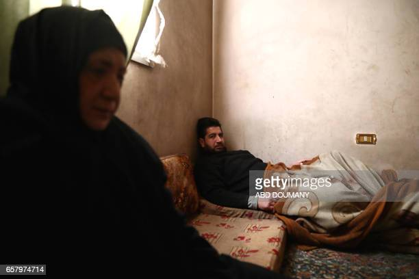 Syrian Naheel a sixtysixyear old widow who was displaced from the alMaliha area due to the ongoing fighting sits next to her son in her home in the...