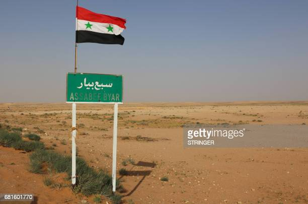 A Syrian national flag flutters above a road sign in the desert area of Saba' Biyar in southeastern Syria near the border with Iraq on May 10 as...