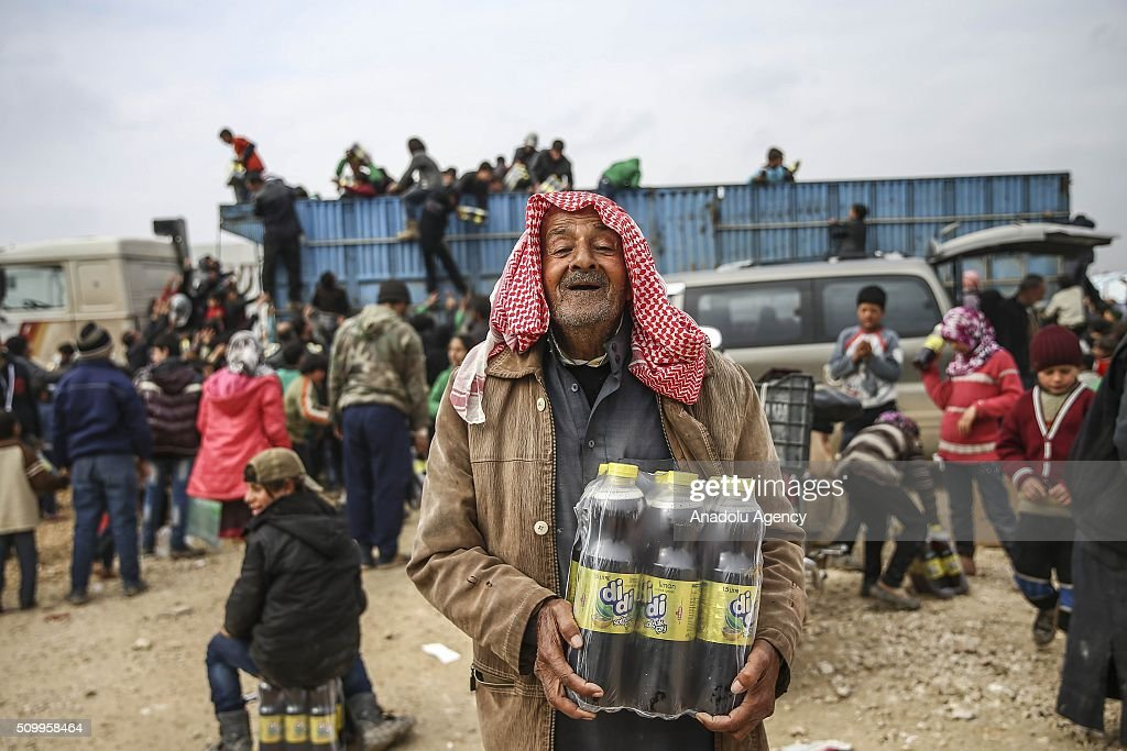 A Syrian old man, who fled bombing in Aleppo, gestures and carry beverages distributed by Turkish Humanitarian organization at a tent city close to the Bab al-Salam border crossing on Turkish-Syrian border near Azaz town of Aleppo, Syria on February 13, 2016. Russian airstrikes have recently forced some 40,000 people to flee their homes in Syrias northern city of Aleppo.