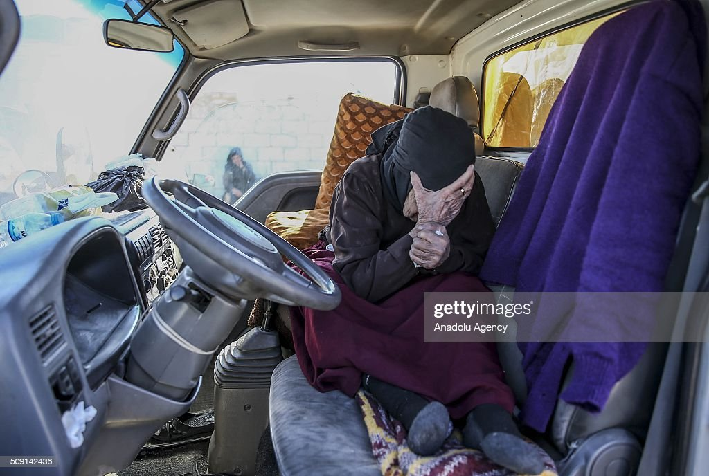 A Syrian old woman who flee the attacks of Assad Regime and Russian air forces, close her face with her hands as she tries to live inside vehicle , at a refugee camp at the Bab al-Salameh border crossing on Turkish-Syrian border near Azaz town of Aleppo, Syria on February 09, 2016.