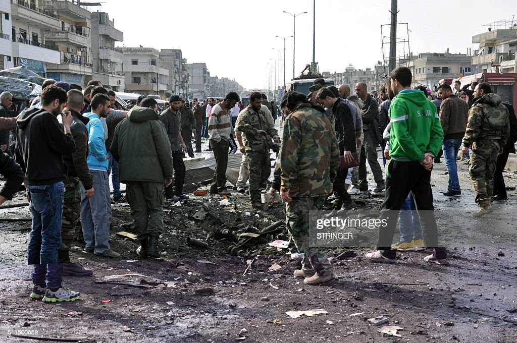 Syrian onlookers and security forces inspect a crater at the site of a double car bomb attack on February 21 2016 in the AlZahraa neighborhood of the...
