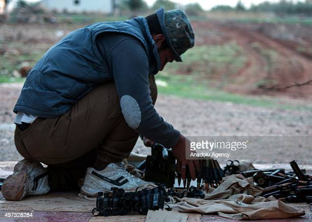 Syrian opponent checks weaponry before attacking Assad regime forces in the AlShaykh Maskin town of Daraa Syria on November 14 2015