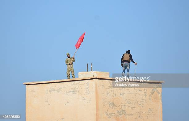 Syrian opponent plants the flag of Sultan Murat Brigades in the village of Harcele seized after clashes with Daesh militants in northern Aleppo Syria...