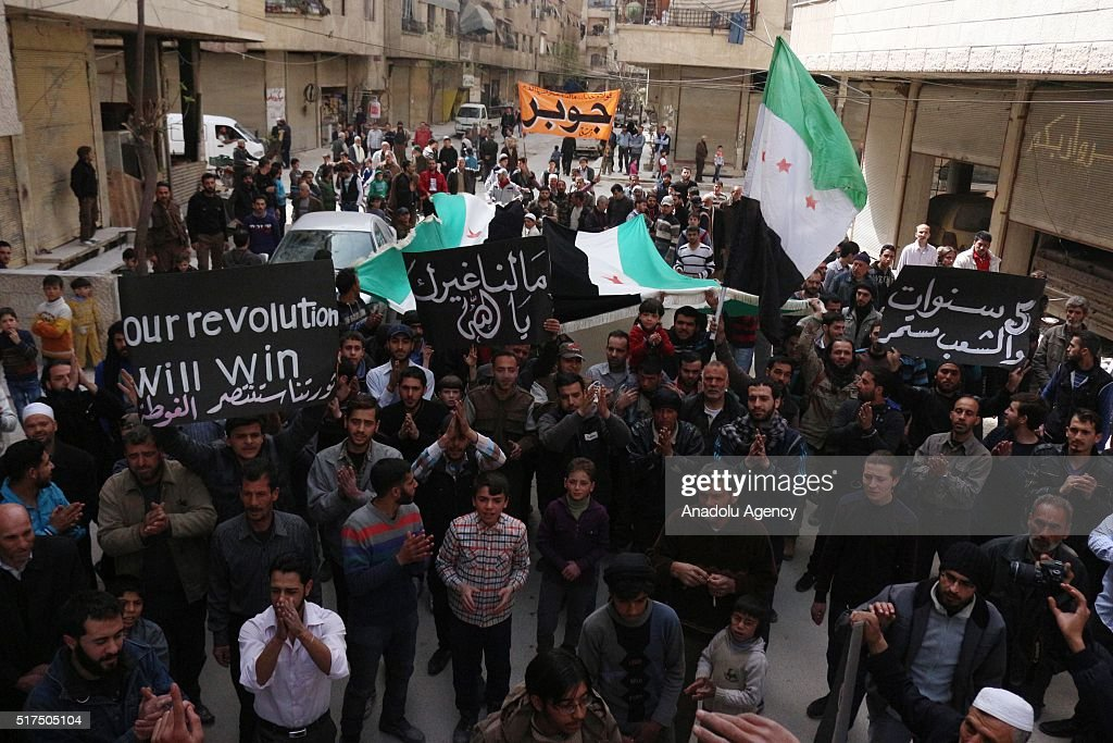 Syrian opponents chant slogans and hold Syrian flags during a protest against Assad Regime after Friday prayers in the opposition controlled Cobar...