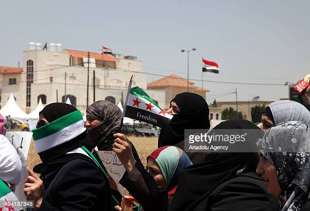 Syrian opponents living in Jordan hold national flags and shout slogans during a protest against the Syrian presidential elections outside the Syrian...