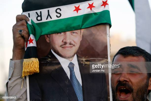 Syrian opposition activist holds up a portrait of Jordan's King Abdullah II durng a rally in support of the expelling of the Syrian ambassador to...