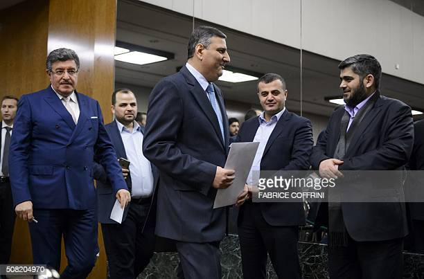 Syrian opposition chief Riad Hijab walks past Chief negotiator for the main Syrian opposition body Mohammed Alloush of Army of Islam rebel group...