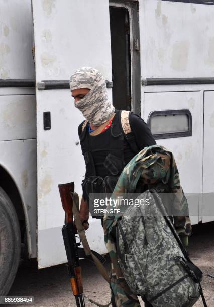 A Syrian opposition fighter arrives at a checkpoint manned by regime forces ahead of their evacuation from Waer neighbourhood the last oppositionheld...