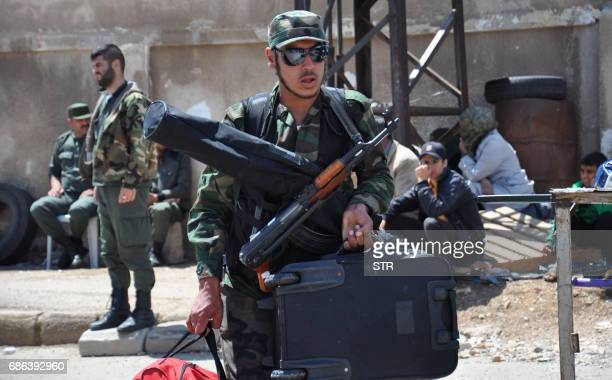 A Syrian opposition fighter arrives at a checkpoint manned by regime forces ahead of his evacuation from the Waer neighbourhood the last...