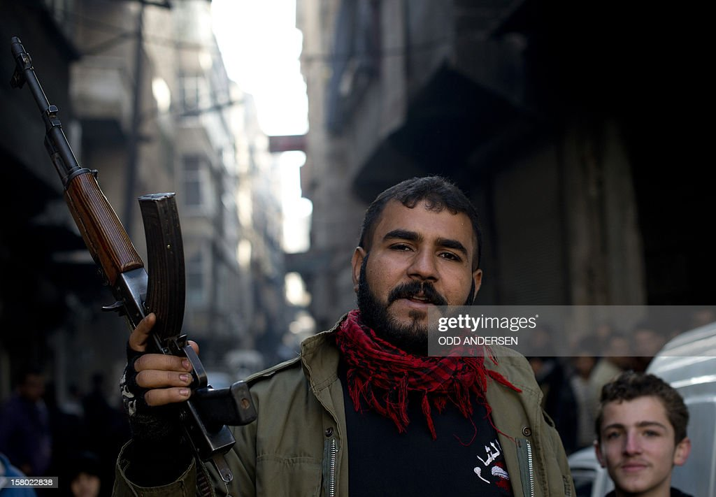 A Syrian opposition fighter monitors the queue as people line up to buy bread outside a bakery in the al-Fardos neighbourhood of the northern Syrian city of Aleppo on December 9, 2012. The cost of basic commodities such as bread and fuel are rising in the city as Syrians have been struggling to continue their daily lives without water or electricity for one week now.