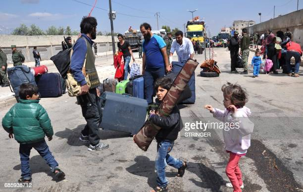 Syrian opposition fighters and their families arrive at a checkpoint manned by regime forces ahead of their evacuation from Waer neighbourhood the...