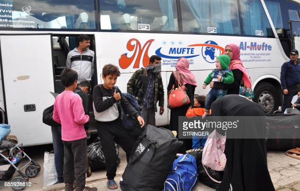 Syrian opposition fighters and their families board a bus at a checkpoint manned by regime forces ahead of their evacuation from Waer neighbourhood...