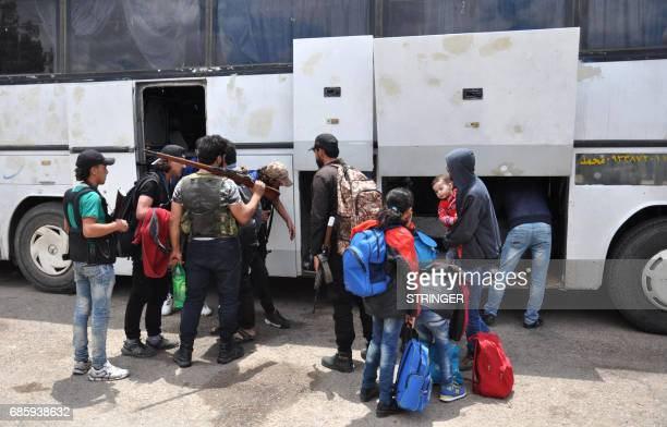 Syrian opposition fighters and their families prepare to board a bus at a checkpoint manned by regime forces ahead of their evacuation from Waer...