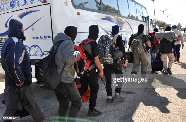 Syrian opposition fighters board a bus ahead of their evacuation from the Waer neighbourhood the last oppositionheld district in the central city of...