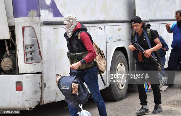 Syrian opposition fighters board a bus at a checkpoint manned by regime forces ahead of their evacuation from Waer neighbourhood the last...