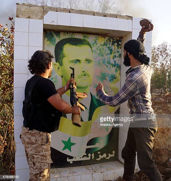 Syrian opposition fighters damage the poster of Syrian President Bashar alAssad after they captured the military Brigade 52 base in Daraa Syria June...