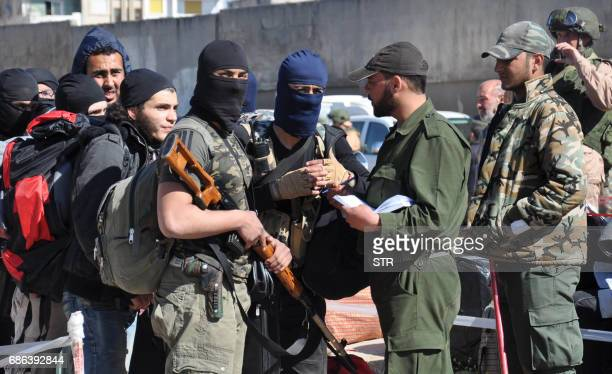 Syrian opposition fighters have their names checked at a checkpoint manned by regime forces ahead of their evacuation from the Waer neighbourhood the...