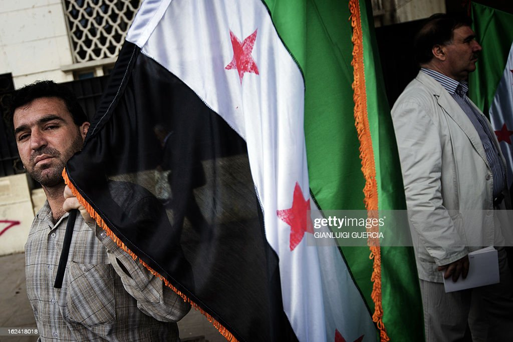 A Syrian opposition figure holds a Syrian flag, currently being used by the Syrian rebels, as they stage a sit-in protest outside the Arab League headquarters in Cairo on February 23, 2013. The opposition National Coalition said on February 22, it will form a government to run 'liberated areas' of Syria, as monitors said more than 12 people were killed when buildings collapsed in a missile strike on the northern city of Aleppo. AFP PHOTO/GIANLUIGI GUERCIA