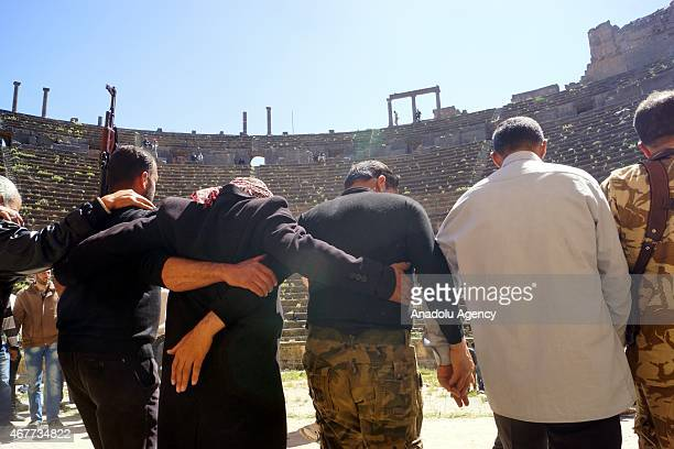 Syrian opposition members celebrate their victory in an antique city after capturing Busra al Sham town of Daraa Syria on March 26 2015