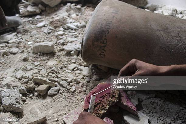 Syrian opposition members collect samples from the site of a suspected chlorine gas attack by Asad regime forces in Jobar region of Damascus Syria on...