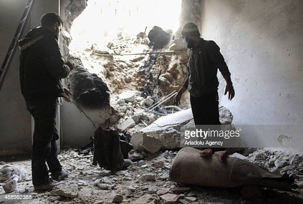 Syrian opposition members inspect the site of a suspected chlorine gas attack by Asad regime forces in Jobar region of Damascus Syria on November 13...