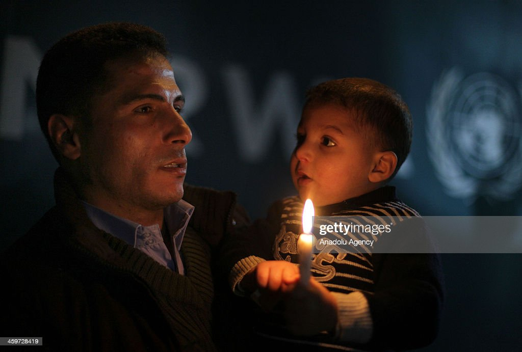 Syrian origin of Palestinian with his kid hold a candle in a protest to show his support to the people living in Yarmouk Palestinian refugee camp, on December 29, 2013, in a UNRWA headquarter, in Gaza City.