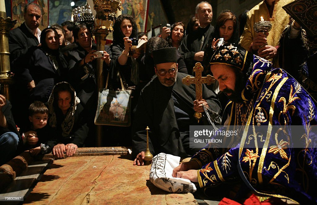 CORRECTION --- Syrian Orthodox Archbishop of Jerusalem, Severias Meliki Morad (R) prays over the Anointing Stone, where according to tradition, Jesus Christ was taken down from the cross and his body was washed after the crucifixion, 06 April 2007, during a symbolic 'Funeral' procession at the Church of the Holy Sepulchre in Jerusalem's Old City. Christian believers around the world mark the holy week of Easter in celebration of the crucifixion and resurrection of Jesus Christ.