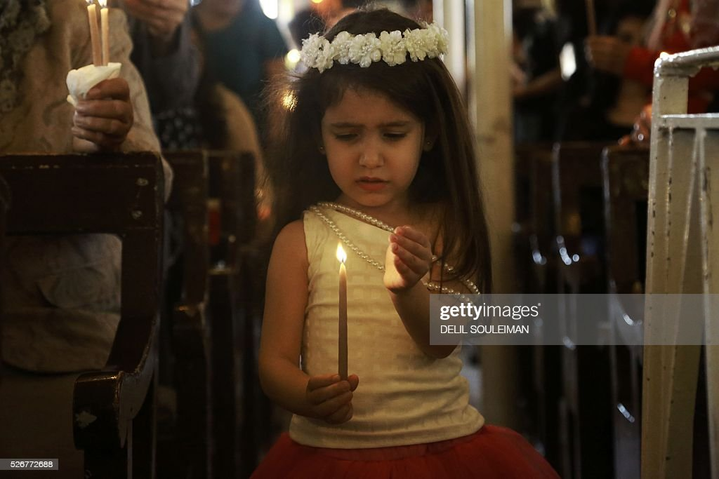 A Syrian Orthodox Christian girl attends a mass in the divided northeastern city of Qamishli during Orthodox Easter celebrations on May 1, 2016. Control of Qamishli is split between Kurdish forces and pro-regime fighters, who agreed a truce last week after several days of rare clashes. / AFP / DELIL