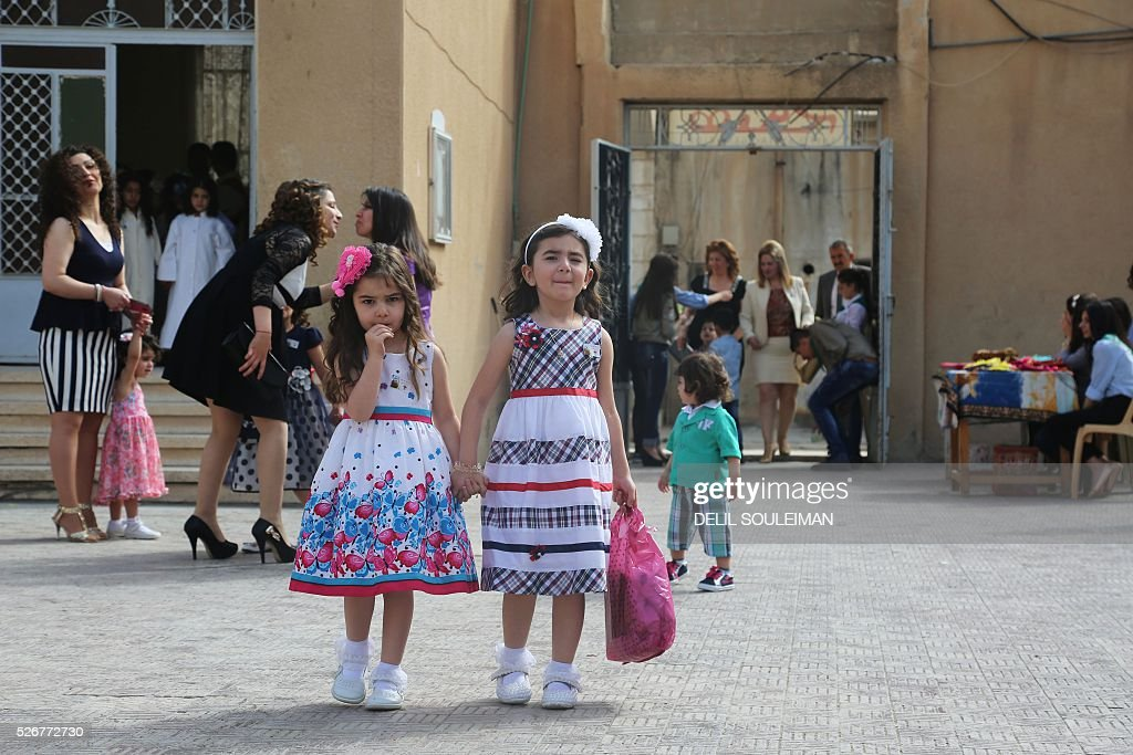 Syrian Orthodox Christian girls arrive to attend a mass in the divided northeastern city of Qamishli during Orthodox Easter celebrations on May 1, 2016. Control of Qamishli is split between Kurdish forces and pro-regime fighters, who agreed a truce last week after several days of rare clashes. / AFP / DELIL