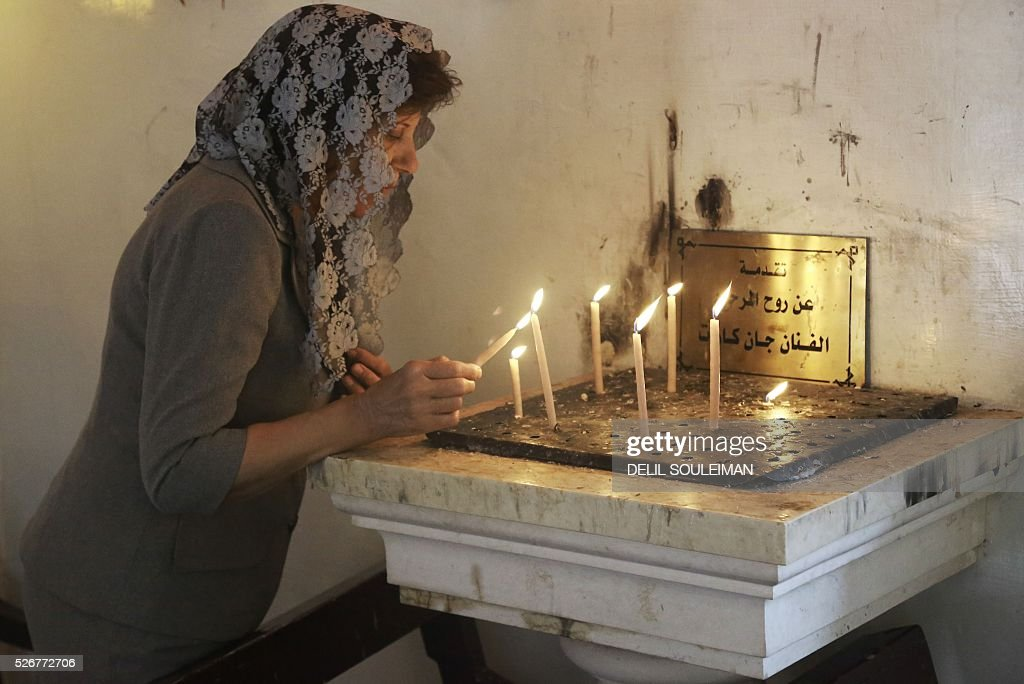 A Syrian Orthodox Christian woman lights a candle before attending a mass in the divided northeastern city of Qamishli during Orthodox Easter celebrations on May 1, 2016. Control of Qamishli is split between Kurdish forces and pro-regime fighters, who agreed a truce last week after several days of rare clashes. / AFP / DELIL