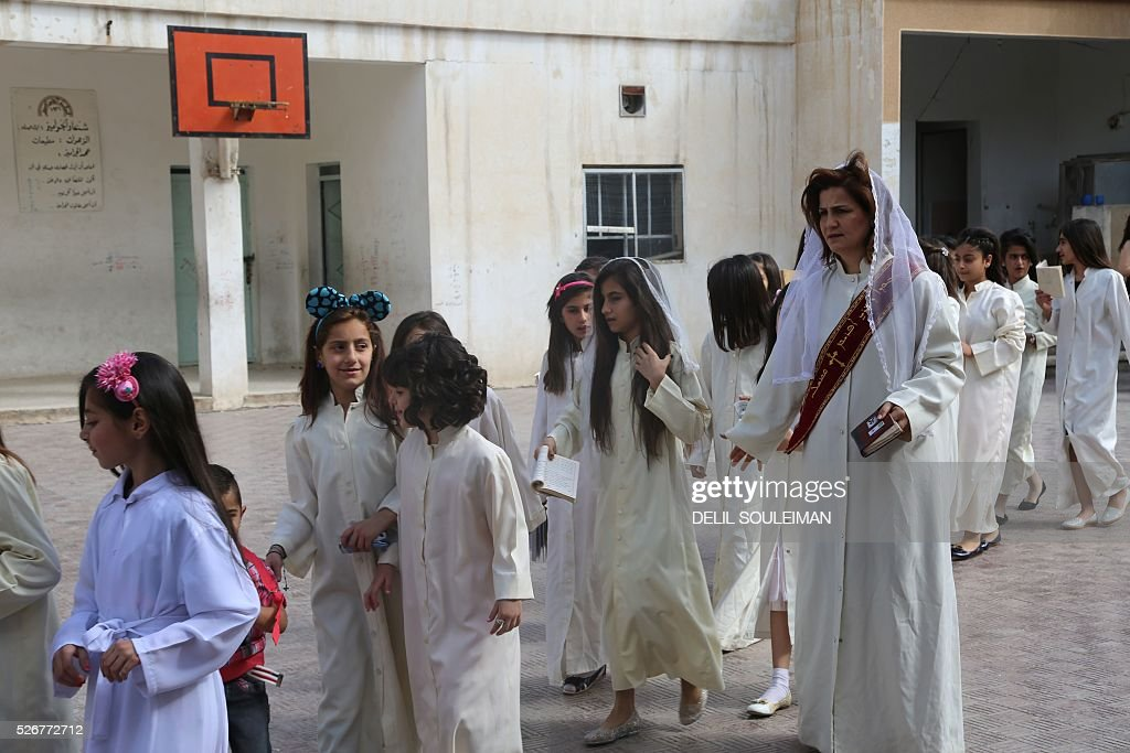 Syrian Orthodox Christians arrive to attend a mass in the divided northeastern city of Qamishli during Orthodox Easter celebrations on May 1, 2016. Control of Qamishli is split between Kurdish forces and pro-regime fighters, who agreed a truce last week after several days of rare clashes. / AFP / DELIL