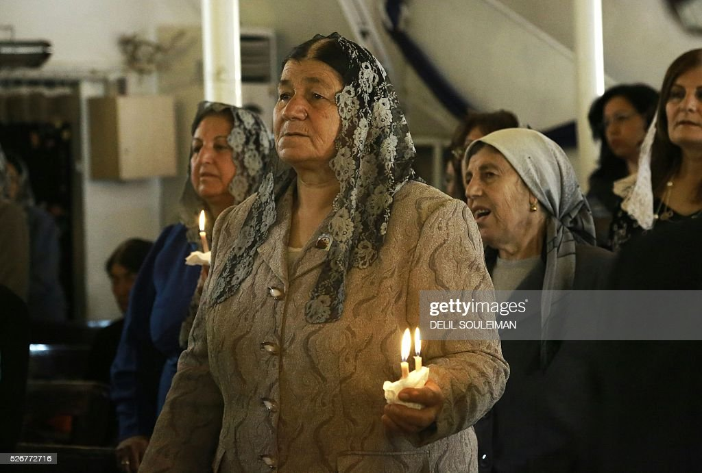 Syrian Orthodox Christians attend a mass in the divided northeastern city of Qamishli during Orthodox Easter celebrations on May 1, 2016. Control of Qamishli is split between Kurdish forces and pro-regime fighters, who agreed a truce last week after several days of rare clashes. / AFP / DELIL
