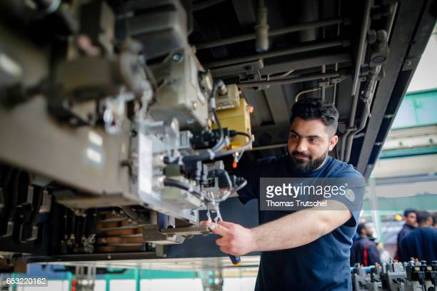 A syrian participant in a training program for refugees poses for a photo at a commuter train repair facility of German state rail carrier Deutsche...