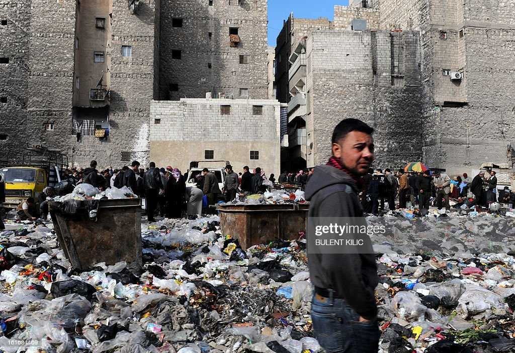 Syrian people are pictured in a bazaar next to a garbage heap in the northern city of Aleppo on February 14, 2013. Syrian Foreign Minister Walid al-Muallem and opposition National Coalition chief Ahmed Moaz al-Khatib will make separate visits to Moscow for talks in the coming weeks, a top Russian diplomat said.