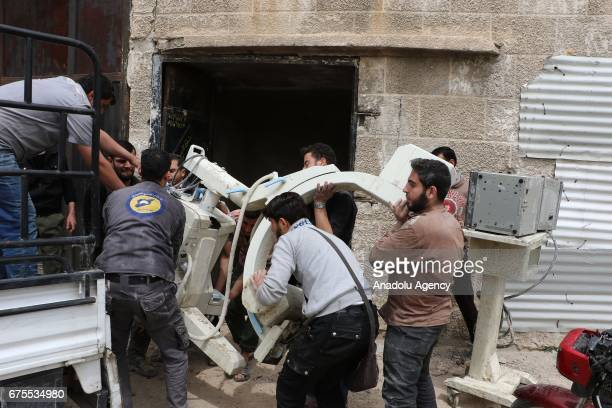 Syrian people carry medical equipment from collapsed Arbin hospital after Assad Regime's airstrike hit residential areas at the Arbin district of...