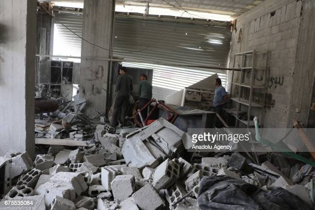 Syrian people inspect wreckage of collapsed Arbin hospital after Assad Regime's airstrike hit residential areas at the Arbin district of Eastern...