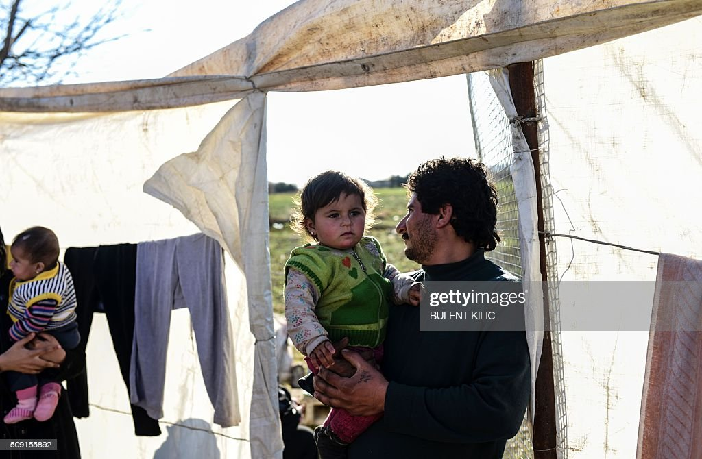 Syrian people living in a makeshift camp inside a farm go about their daily life near Oncupinar crossing gate, stand on February 9, 2016, in Kilis. Around 30,000 Syrians are at the Turkish border after fleeing a Russia-backed regime offensive on the northern region of Aleppo, Turkish Prime Minister Ahmet Davutoglu said on February 8, as his country faces mounting pressure to open its border. Davutoglu said the refugees would be admitted if need be, although Turkey should not be expected 'to shoulder the refugee issue alone.'. / AFP / BULENT KILIC