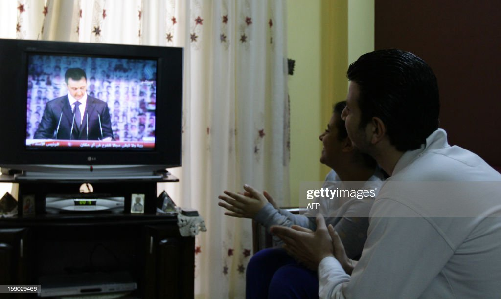 Syrian people react as they watch Syria's embattled President Bashar al-Assad making a public address on the state-run Syrian TV, on January 6, 2013 in Damascus. Bashar al-Assad in a rare speech Sunday denounced the opposition as 'slaves' of the West and called for a national dialogue conference to be followed by a referendum on a national charter and parliamentary elections.