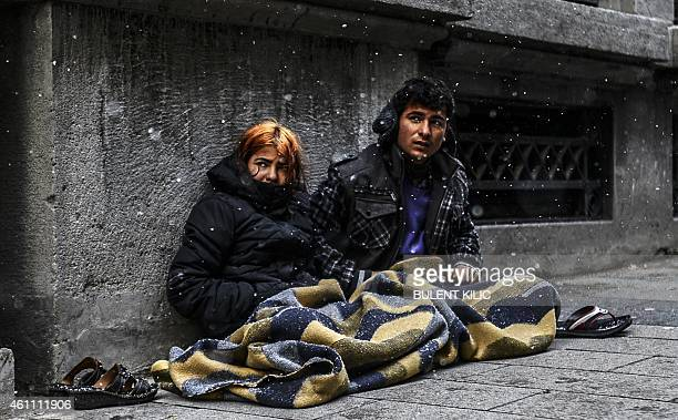 Syrian people sit on the sidewalk under the snow in Istanbul on January 7 2015 Heavy snowfall descended on large parts of Turkey on January 6...